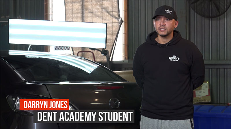 "Man standing next to a car in a garage with The Dent Academy logo on his apparel, with the text ""Darryn Jones - Dent Academy Student"" beneath him."