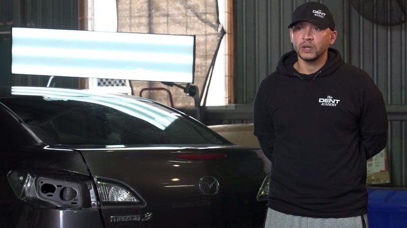 Man standing next to a car in a garage with The Dent Academy logo on his apparel.
