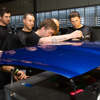 Five men standing next to a car in a garage with The Dent Academy logo on their apparel learning how to fix a hail damaged vehicle.