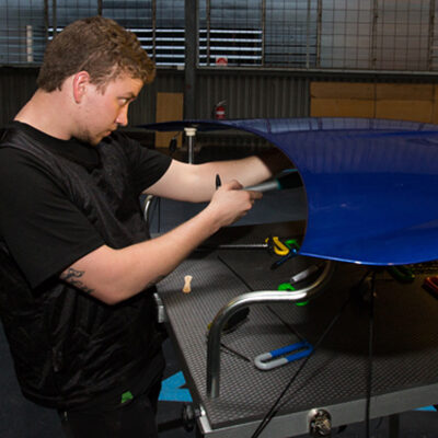 Man fixing the hood of a hail damaged car using paintless dent removal techniques.