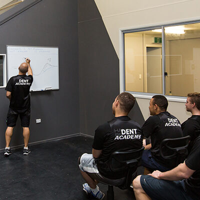 Five men in The Dent Academy branded apparel learning from a whiteboard presentation.