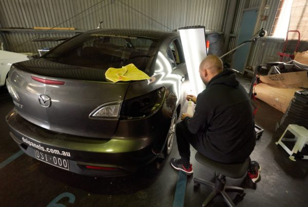 Man in a garage repairing a hail damaged vehicle using paintless dent removal techniques.